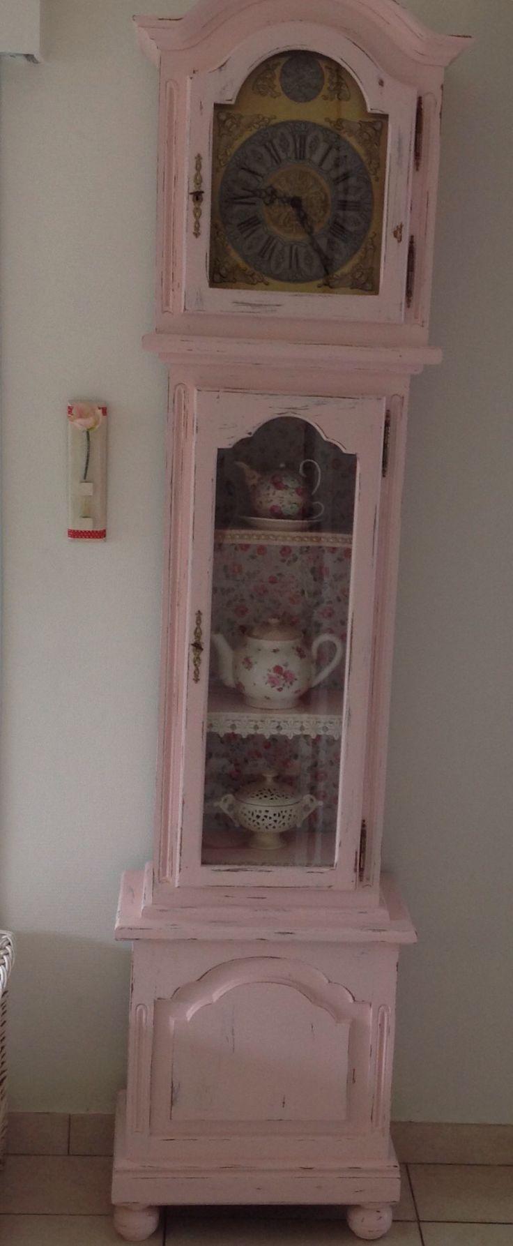 Oude, staande klok in roze jasje