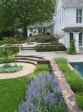 Small stepped down garden from House,  hedged in a lavender plant & boxwood. Love the circular feature.