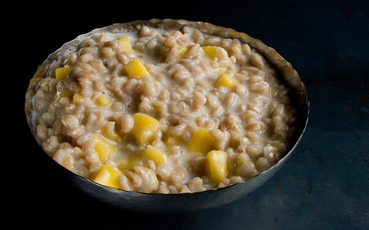 Nutty farro slow-cooked in coconut milk and topped with zesty mango for a creamy but vegan breakfast porridge.