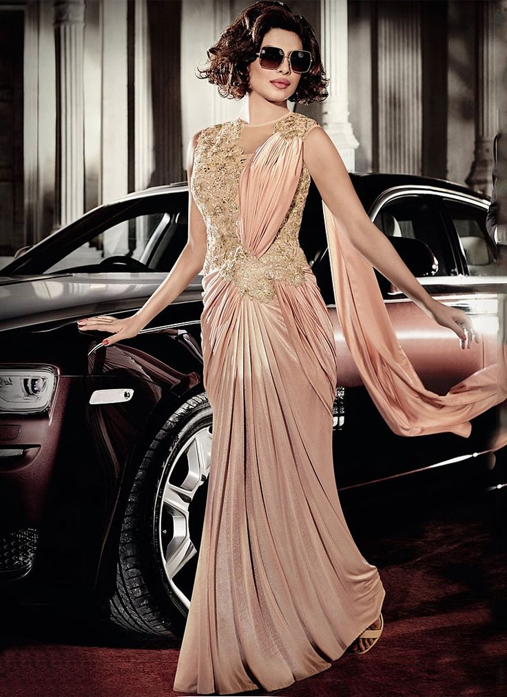 Featuring Priyanka Chopra lycra saree style gown adorned with intricate resham,zari embroidery, and sequins.It is paired with matching lycra bottom. This gown can be stitched upto size 44. For stitching enquiries, please email us at customercare@hunardesigns.com  |…