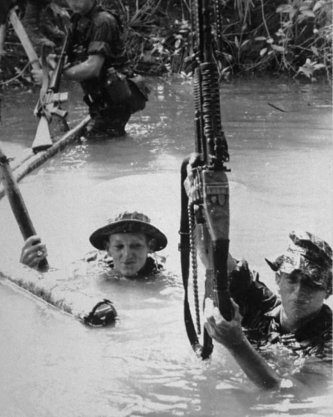 Members of a long range recon patrol (LRRP) crossing a body of water. ~ Vietnam War
