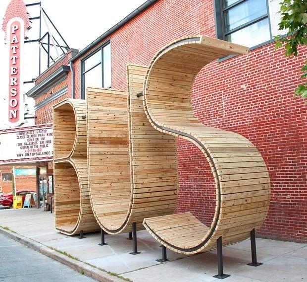 Oui, cette installation est un arrêt de BUS ! Trois grandes sculptures comme celle-ci ont été installées dans la ville de Baltimore. Créées par mmmm…, ces lettres gigantesques font 4,3 m de haut pour 2,1 m de large. En bois et acier, elles peuvent accueillir jusqu'à quatre personnes.