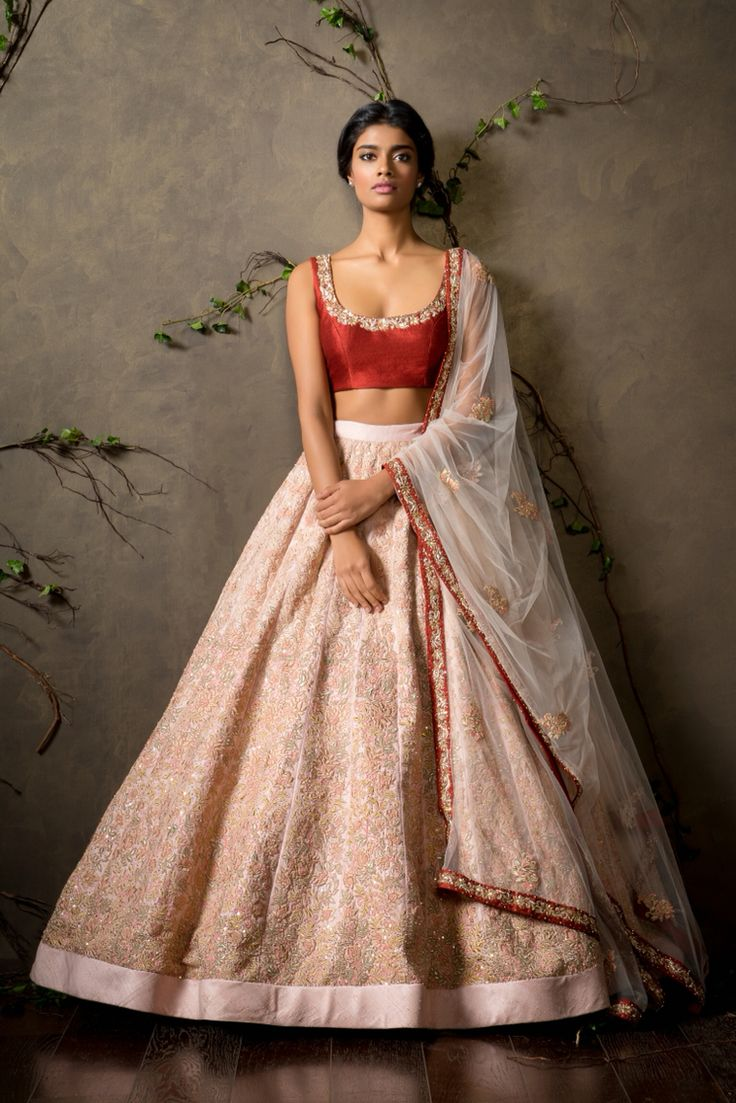 A beautiful peach pearl raw silk high waisted lehenga with elegant tone on tone floral embroidery all over teamed with a pompeien red choli and a tulle dupatta with hints of gold sequins and pearls all over completed the fairytale look.  Sales@shyamalbhumika.com   www.shyamalbhumika.com