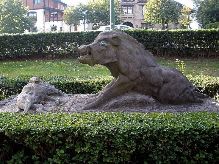 """Grupo escultórico de granito negro, del que fue autor Eduardo Figueroa, conde de Yebes, en 1948, a petición del conde de Arteche para el jardín de su finca """"Kaiondo"""". Recrea una escena de caza, en la que un jabalí acosado da muerte a varios perros.  La escultura fue donada al Ayuntamiento de Getxo en 1967 y colocada en los jardines de la Avenida Zugatzarte, nº 42."""