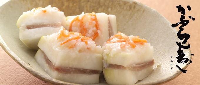金城かぶら寿し@ 金沢 - 四十萬谷本舗    金沢の冬の味覚「かぶらずし」は馴れすしの一種とされる。こちらは馴れを促進するために米麹が入るため早く味が出る。  「前田の殿様が深谷温泉へ湯治に来られた時の料理の一つとして出された」などの言い伝えが残っているが、起源はさだかではない。 記録としては、年賀の客を饗応する料理として「なまこ、このわた、かぶら鮓」とあり、当時は魚屋が漬け込み正月用の珍味としてお得意様へ贈っていた。かぶら寿しは高い身分の者が食し、一般の人たちは大根寿しを食べていたと考えられる。  明治維新後、大正末期以降は昭和30年頃まで一般家庭でも盛んに漬けられるようになり、各家庭の味の違いがお互いの味自慢になっていた。 現在は漬物専門店の正月料理の主食品として冬の味覚を伝えている。