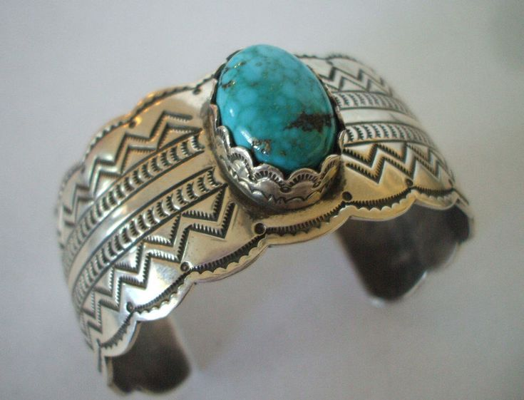 "SIGNED NAVAJO BRACELET. SIGNED: L. JACKSON (Navajo). A gorgeous cabochon of lightly webbed turquoise is at the center of a raised and stamped bezel. MEASUREMENTS: Interior of the cuff measures 5 7/8"". 