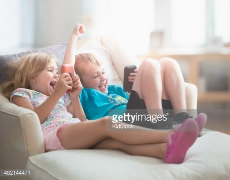 Family using electronic gadgets in a living room : Stockfoto