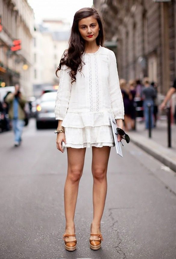 An all white ensemble featuring a peplum long sleeve top and skirt is worn with peep-toe platforms.