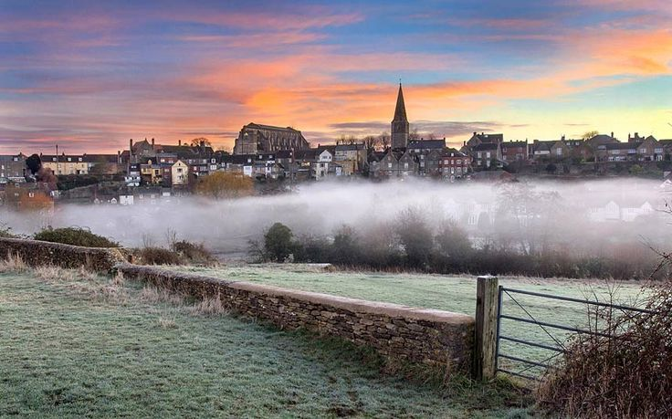 A plume of mist rolls across a field in front of the Wiltshire village of Malmesbury