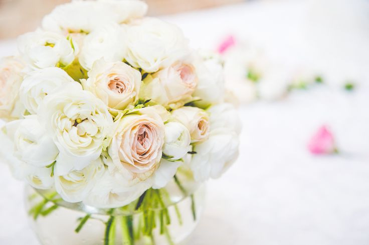 Signing table arrangement of roses and ranunculus in a glass fishbowl at the wedding ceremony.