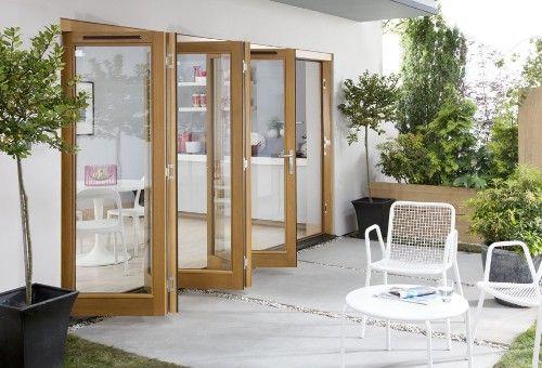 Desain eksterior rumah minimalis pintu kaca modern, bingkai kayu dan kursi teras putih