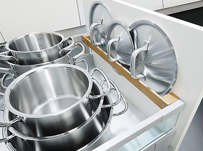 Des placards de cuisine qui accueillent des supports pour couvercles
