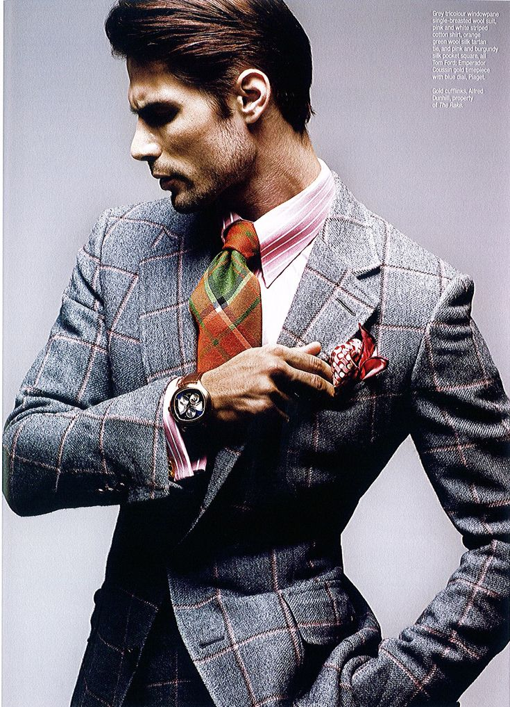 Grey tricolour windowpane single-breasted wool suit, pink & white striped cotton shirt, orange-green wool silk tartan tie, and pink & burgundy silk pocket sq. All Tom Ford. Emperador coussin gold timepiece with blue dial, Piaget. Gold cufflinks- Dunhill.