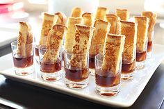 """We lined up a bunch of """"bitty bite"""" glasses on a large square platter and filled them with organic maple syrup. Then, we put a French toast stick in each glass. I think it's a fun, modern take on French toast, and the whole presentation came out looking great."""