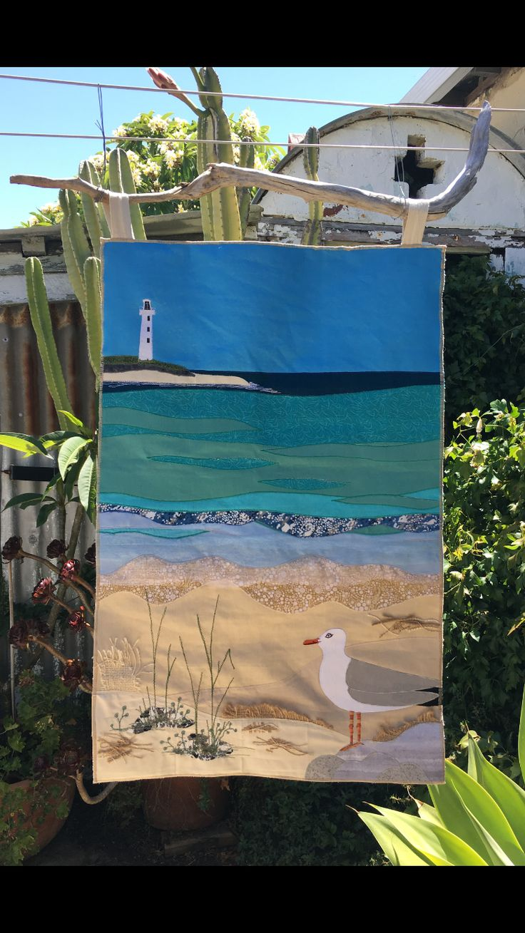 Coastal scene designed for my Dad's 70th birthday. Rottnest Island lighthouse in the background. Seagull in front. Hand embroidery, free motion machine stitching and applique. Driftwood for hanger.