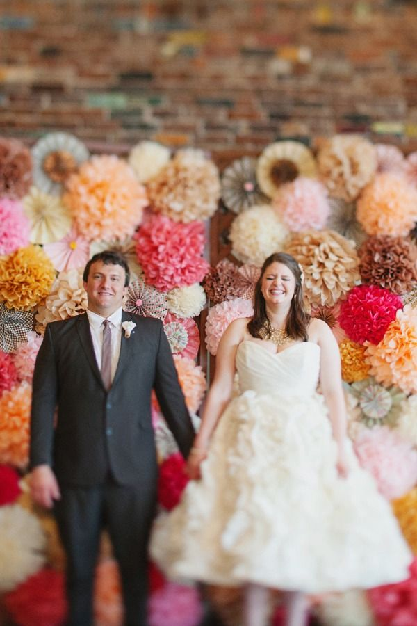 Very creative backdrop idea. These two got married in front of their custom made whimsical wall of tissue and pinwheels!