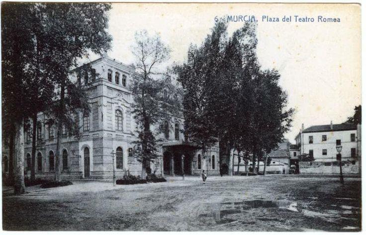 fotografia data de 1.920 - 1.930, y nos muestra una vista de la fachada principal del Teatro Romea, ademas del lateral de la calle Ángel Guirao y al fondo el Arco de Santo Domingo, que une el Palacio de Almodóvar y la capilla del Rosario.