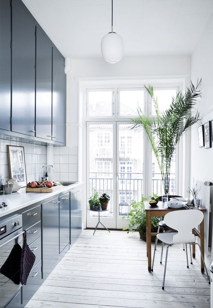 Windows from floor to ceiling gives enormous light to this stylish and simple kitchen. Bring the nature inside by having plants in several sizes.