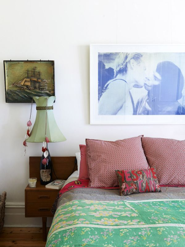 Bedroom with vintage green Kantha quilt and art print above bed.