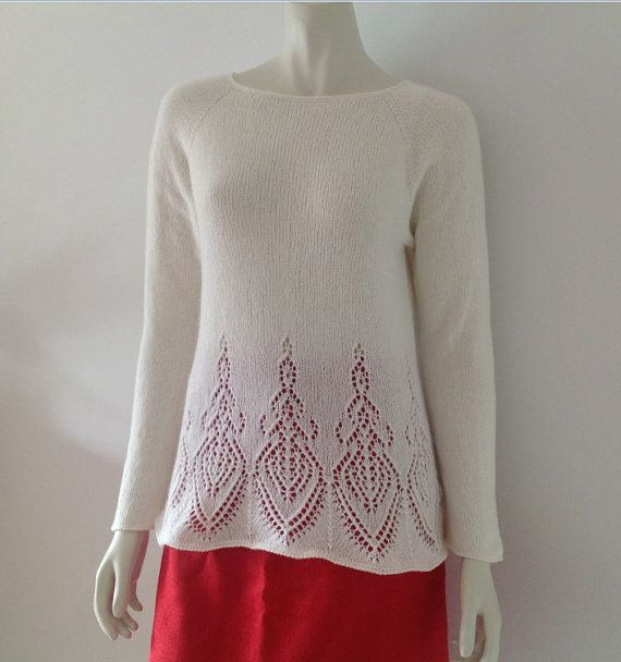 Off-white handknitted pullover with lace pattern. The pullover is knitted with a yarn consisting of 40% angora, 40% viscose and other fibres. It has