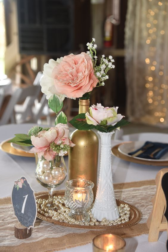 Vintage, elegant, centerpiece. milk glass, gold wine bottle, pearls, wine glass, peach rose, pink peony, babies breath, navy blue napkin, gold charger
