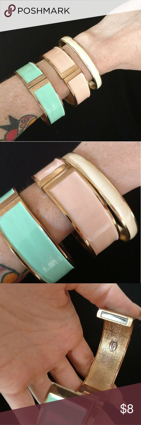 Set of 3 Aldo pastel bangles These bracelets are super fun and versatile for any spring or summer outfit. The hardware on them is all gold so they're easier to layer and mix and match with other bracelets and jewelry. The two wide Bangles open up and secure together with a magnet. One is mint green one is baby pink and one is ivory, they all have a shiny lacquered kind of finish. They're very sturdy and durable, they're definitely not liable to break or crack easily despite being from a shoe…