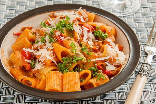 Ingrediënten: - 400 g rigatoni - 2 el olijfolie - 1 ui, gesnipperd - 2 tenen knoflook, fijngehakt - 300 g rundergehakt - 1 blikje tomatenpuree (70 g) - 2 blikken gepelde tomaten ( a 400 g) - 150 g gor