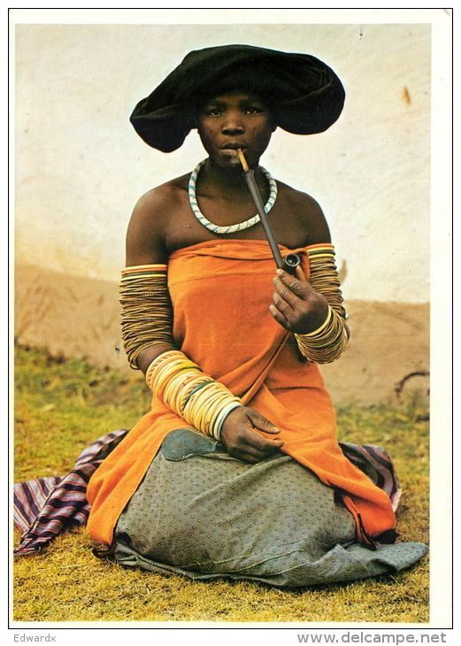 Africa | Portrait of a Xhosa woman wearing traditional clothes, jewelry and arm rings smoking her pipe, South Africa | Postcard; publisher Protea Colours. No 896 #beads