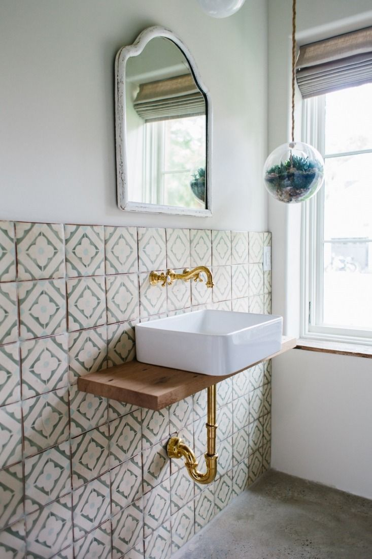 Guest bathroom with green patterned tiles and simple white ceramic sink.