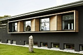 Fassadenausschnitt eines Hauses - graue Wand und Fensterband mit umlaufendem Holzrahmen und Garten mit kleinem Obelisken