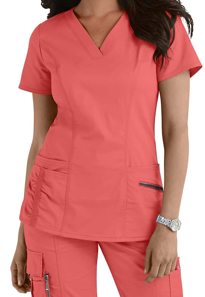 How cute is our Beyond Scrubs Ellie v-neck scrub top in Coral? With its flattering design and roomy pockets, we think this will be one of your new favorite tops! |Scrubs & Beyond