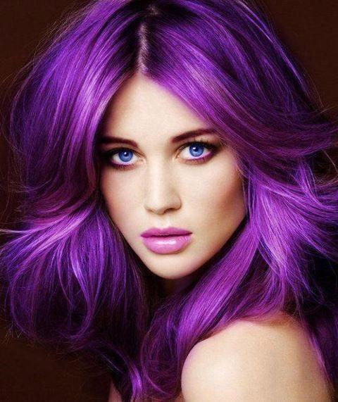 Cette femme aux longs cheveux porte magnifiquement une superbe coloration violette, qui s'assortit à merveille à son teint clair. Le mélange du bleu des yeux, du violet des cheveux et du rose des lèvres crée un tout très harmonieux.