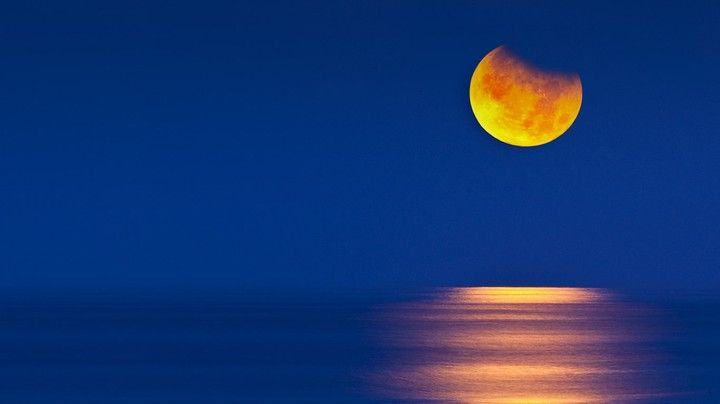 Partial eclipse of the moon setting over the Gulf of Mexico