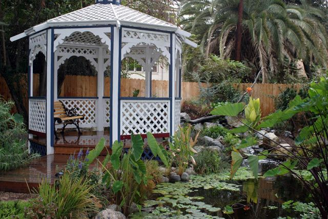 A garden bench tucked inside a pondside cottage gazebo creates the perfect place to relax outside!