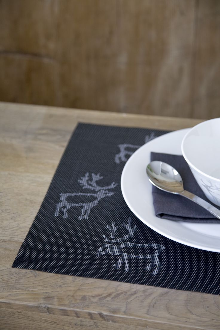 Saaga Coated Placemat | Pentik | The kitchen textiles of Saaga series bring a hint of northern touch to your table setting. Deisgned by Minna Niskakangas, the reindeer pattern of Saaga has been inspired by northern rock paintings and warm gray shades of deadwood.