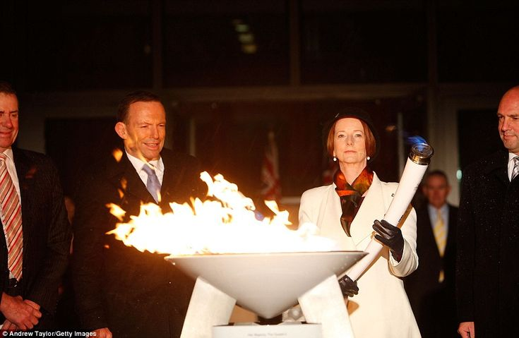 Australian Prime Minister Julia Gillard and opposition Leader Tony Abbott jointly light a ceremonial beacon to mark the Queen's Diamond Jubilee at Parliament House in Canberra
