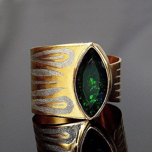 Bardzo efektowny bogaty pierścionek ze srebra złoconego z szlachetnym opalem etiopskim (o wymiarach 16x8mm). Kamień o przepięknej urodzie - zielono-niebieska opalizacja z domieszką czerwieni podkreślona przez czarne tło. Zdjęcia nie są w stanie oddać głębi i gry barw. Obrączka pierścionka jest asymetryczna - podchodzi pod kształt łezki, dzięki czemu układa się stabilnie na palcu. Pasek obrączki zwęża się stopniowo od 16 do 8,5mm. Na obrączce został wygrawerowany ozdobny wzór. Rozmiar ...