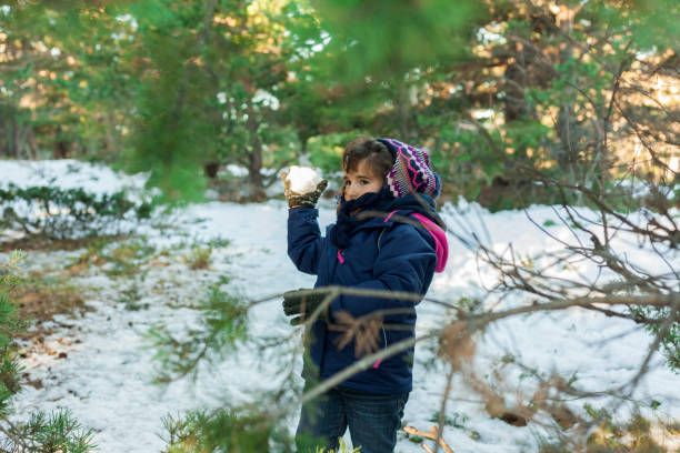 children throwing snow balls in the snowcovered mountain