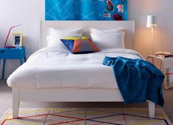 Camera da letto dallo stile moderno con struttura letto bianca, copripiumino bianco, tessili in blu vivo e comodino in blu vivo.