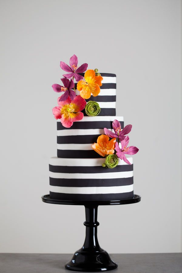Black and white fondant stripes, done with a hand-cut strips kind of look in mind. The brightly colored sugar flowers include poppies, clema...