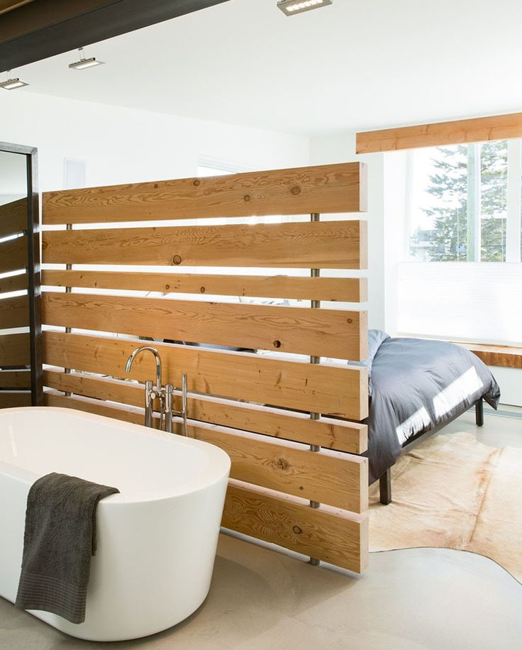 15 Creative Ideas For Room Dividers // A wood panel wall separates the tub from the bed in one of Canada's greenest homes.