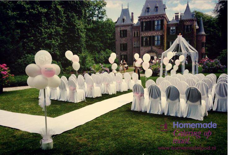 Een ceremonie opstelling in de tuin van Kasteel Keukenhof. Wit afgerukte klassieke stoelen, witte loper, ballon decoratie in de kleuren wit en zacht roze en een prieel versierd met wit organza. Het Kasteel op de achtergrond.