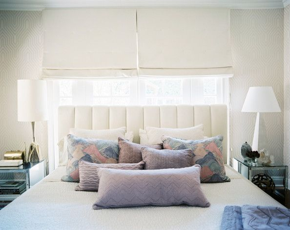When a room's configuration forces you to place your bed in front of a window, frame the headboard with clean-lined shades in a complimentar...