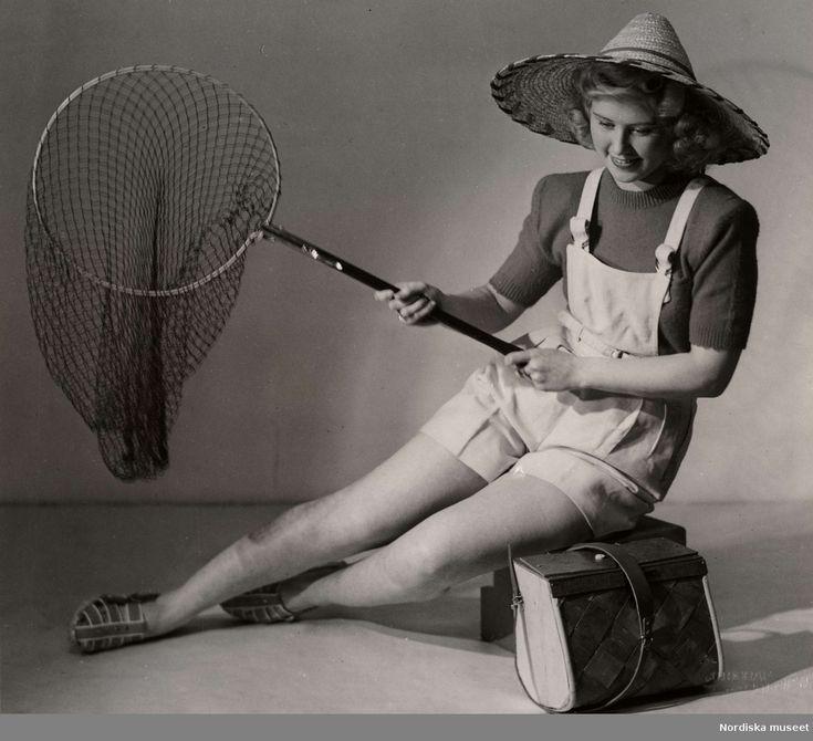 Sommarmode från varuhuset Nordiska Kompaniet i Stockholm 1944. En kvinnlig modell iklädd korta hängselbyxor, tröja, stråhatt och sandaler sitter med en fiskehåv i handen. Vid hennes sida står en väska av flätat näver. Fotograf: Erik Holmén.