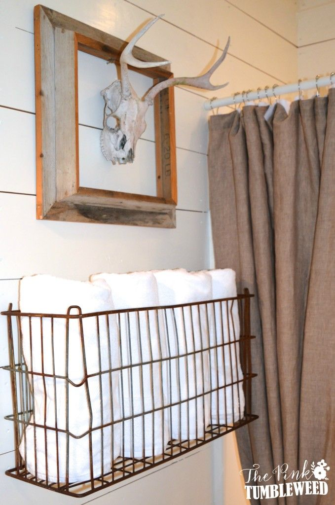 Vintage metal basket mounted to the wall for towels