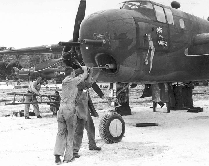 Armorer cleaning the bore of a 75mm cannon mounted in a B-25G Mitchell bomber of the 820th Bomb Squadron, Tarawa, Gilbert Islands, March-Ap…
