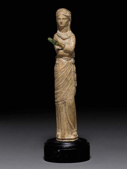 A ROMAN BONE FIGURE OF APHRODITE   Circa 2nd Century A.D.   The goddess depicted wearing a peplos under a himation which wraps around her waist and is pulled up over the back of the head, wearing a crescentic diadem in her center-parted hair, her pupils indicated, the lips parted, holding a pinecone (?) in her separately-made left hand, which is inserted into a mortise at the end of her arm, standing on a low integral plinth with a concave side molding
