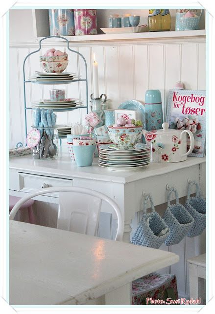 Cute white and aqua kitchen. Love the three aqua baskets hanging from the side of the white table.