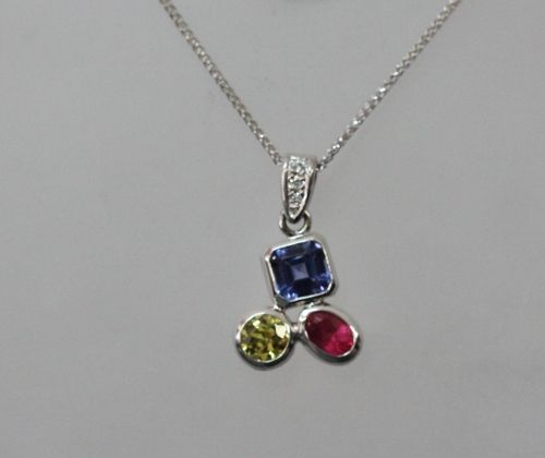 Beautiful handmade pendant, telling the story of a family. Made with recycled 18 carat white gold, the pendant features birthstone gems to represent each family member, plus some Argyle white diamonds for sparkle. We have an Australian yellow Sapphire, a gorgeous Tanzanite and a fair trade Ruby.
