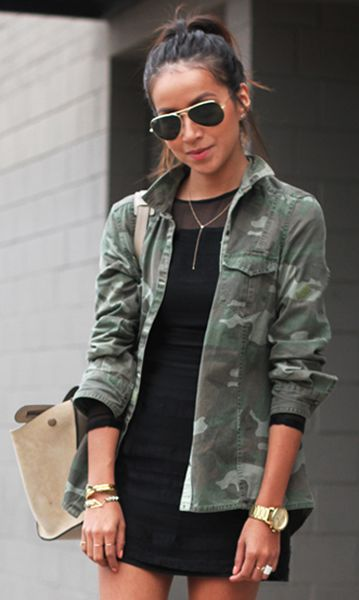 black long sleeved dress with camo jacket worn with a gold necklace and aviator sunglasses
